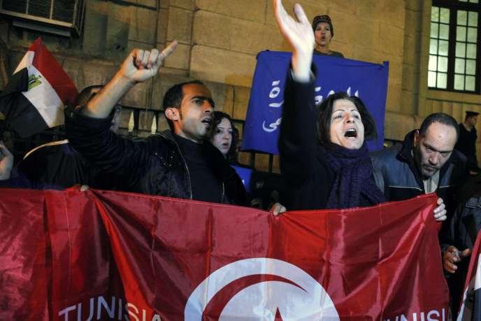 Des Égyptiens manifestent contre le gouvernement en brandissant un drapeau tunisien, le 17 janvier, au Caire.