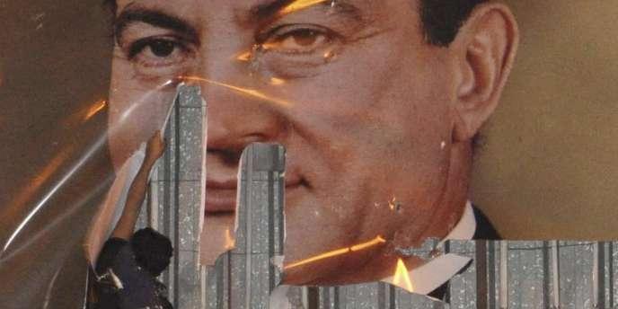 Un manifestant déchire une affiche à l'effigie du président égyptien Hosni Moubarak, mardi 25 janvier 2011, à Alexandrie.