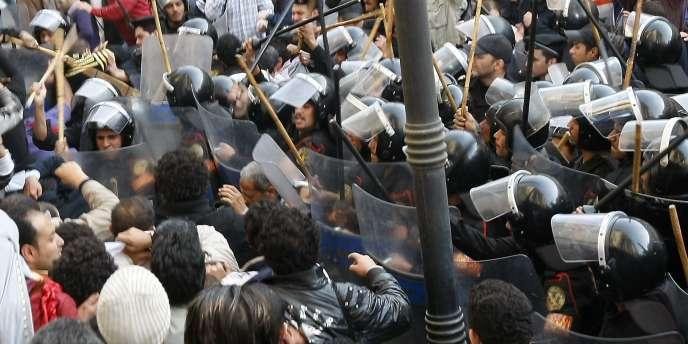 Des policiers répriment des manifestants anti-gouvernement, mercredi 26 janvier, au Caire.