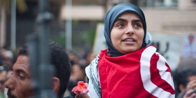 Une femme, enroulée dans le drapeau tunisien, manifeste dans une rue de Tunis, le 20 janvier 2011.