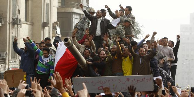 Des opposants à Moubarak sur un char de l'armée au Caire, samedi 29 janvier.