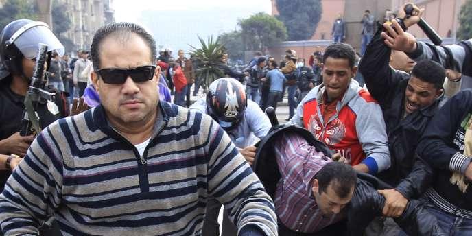 Un policier en civil tente de confisquer l'appareil photo d'un photographe de Reuters, tandis qu'un manifestant se fait agresser.