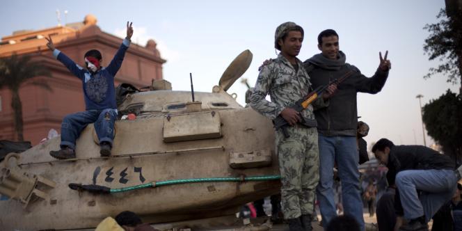 Des manifestants prennent la pose au côté d'un soldat égyptien, samedi matin 12 février, au lendemain de la démission de Hosni Moubarak.