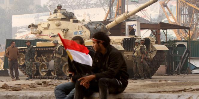 Des manifestants et un blindé de l'armée égyptienne, aux abords du siège de la télévision publique égyptienne, au Caire, vendredi 11 février.
