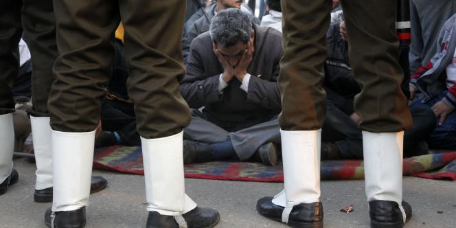 Des militaires encerclent un groupe de protestataires qui continuent d'occuper la place Tahrir, au Caire, dimanche 13 février.