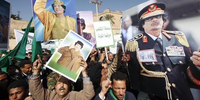 Des manifestants pro-Kadhafi exhibent le portrait du dirigeant libyen lors d'une contre-manifestation organisée à Tripoli, jeudi 17 février.