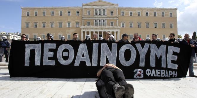 Devant le Parlement grec à Athènes, des manifestants tiennent une banderole sur laquelle on peut lire