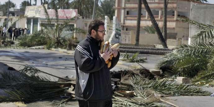 Un habitant de Tripoli fait des stocks de pain, samedi 26 février.
