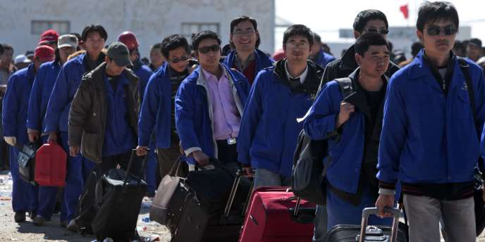 Des travailleurs chinois passent la frontière tuniso-libyenne, à Ras Ajdir (Tunisie), dimanche 27 février.
