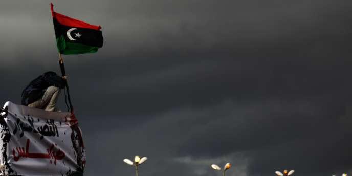Un manifestant anti-Kadhafi exhibe l'ancien drapeau libyen, à Benghazi, le 27 février 2011.