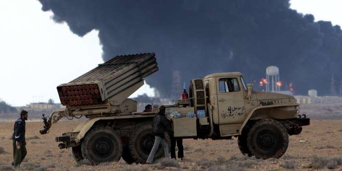 Des insurgés se préparent à affronter les forces pro-Kadhafi, devant un terminal pétrolier bombardé, près de Ras Lanouf, mercredi 9 mars.