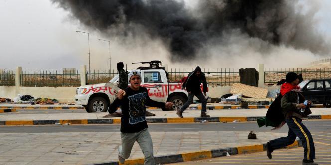 Des sympathisants des rebelles libyens s'enfuient après un bombardement aérien à Ras Lanouf, jeudi 10 mars.