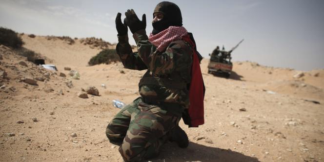 Près de Ras Lanouf, un homme prie après la déroute de dizaines de rebelles face à l'armée libyenne.