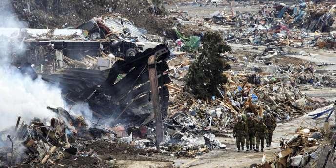 Des soldats marchent au milieu des débris causés par le séisme du 11 mars, samedi 12 mars, à Minamisanriku, au Japon.