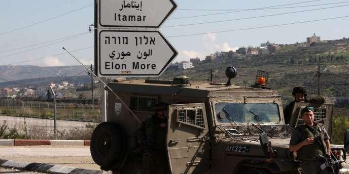 Des militaires israéliens surveillent la route menant à la colonoie d'Itamar où une famille de colon a été assassinée, dans la nuit du vendredi au samedi 12 mars.