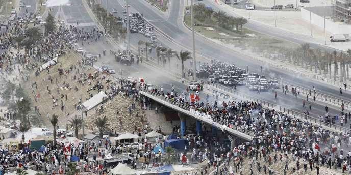 Les manifestants aux prises avec les forces de police sur la place de la Perle à Manama, capitale du Bahrein, dimanche 13 mars.