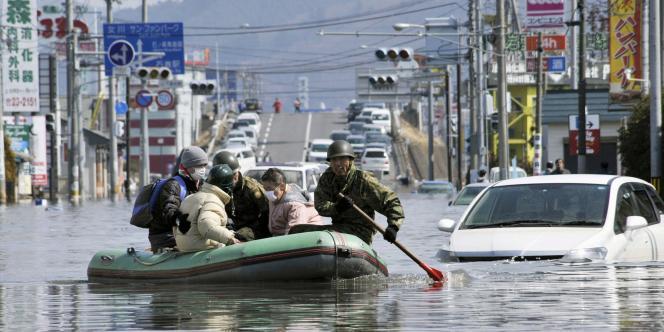 Des secouristes japonais, dimanche 13 mars, à Ishinomaki.