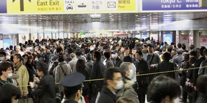 Des passagers attendent de pouvoir prendre un train à la station de Yokohoma, près de Tokyo, lundi 14 mars, alors que le trafic restait très perturbé.