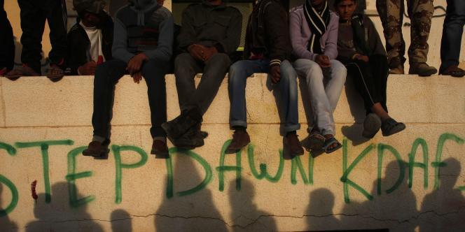 Des manifestants anti-Kadhadi, assis sur un mur de la ville de Tobrouk, à l'est de Tripoli, le 14 mars 2011.