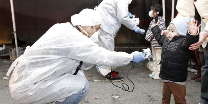 Des enfants évacués de la zone interdite autour de la centrale de Fukushima sont examinés, le 13 mars 2011.