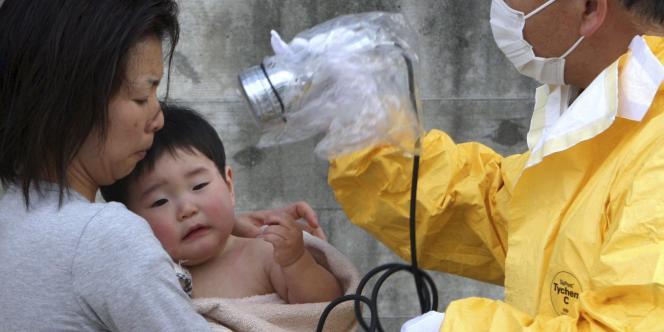 Un enfant subit des tests de radiation à Nihonmatsu, dans le nord du Japon, le 14 mars.