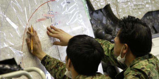 Au quartier général d'urgence et de secours à Fukushima, les responsables du ministère de la défense tentent de situer les zones potentiellement affectées par les rejets radioactifs.