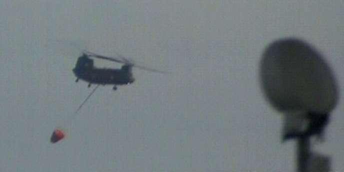 Un hélicoptère de l'armée japonaise déverse de l'eau dans un réacteur de la centrale de Fukushima.