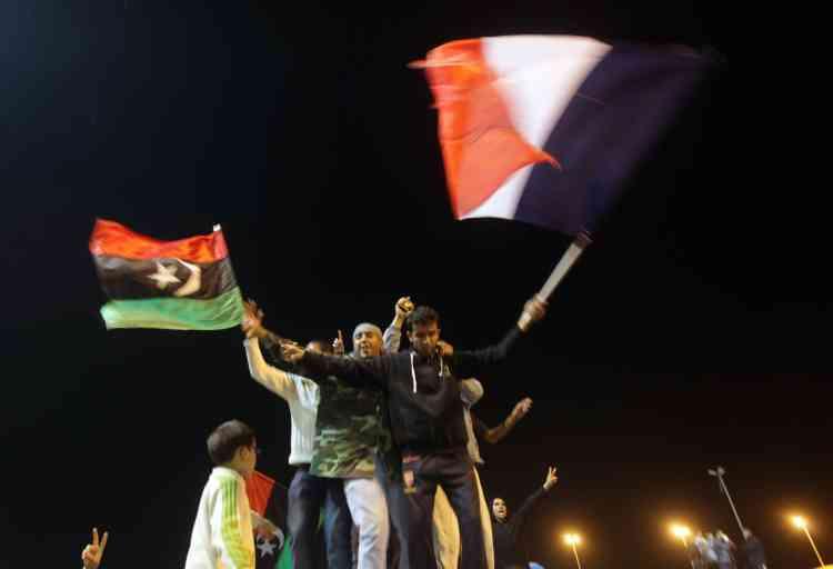 Des Libyens brandissent le drapeau de l'ancienne monarchie libyenne et le drapeau français, mardi 17 mars à Benghazi.