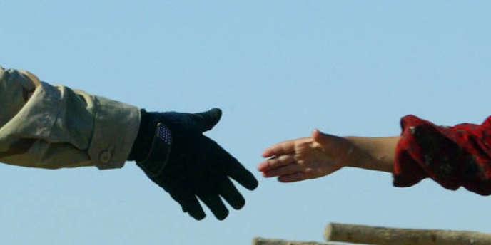 Un soldat américain et un enfant irakien se serrent la main, le 21 novembre 2003.