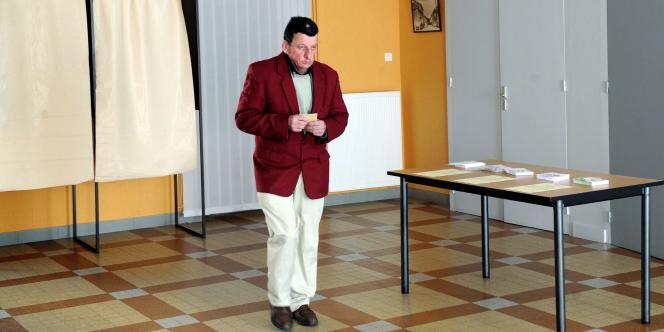 Un homme sort de l'isoloir dimanche dans un bureau de vote de la commune de Mardore (Rhône), lors du premier tour des élections cantonales.