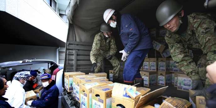 Des cartons contenant des bouteilles d'eau sont déchargés pour les sinistrés du village de Iitate dans le département de Fukushima.
