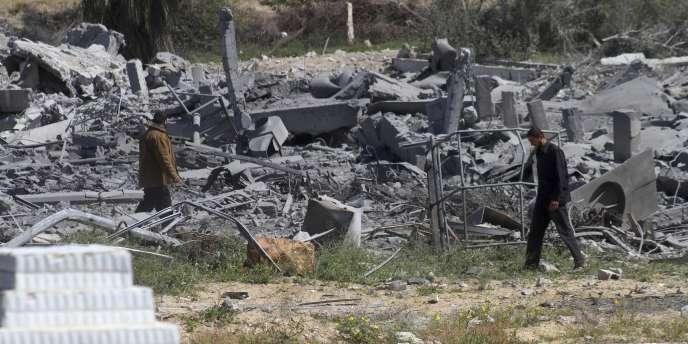 Un officier de sécurité palestinien du Hamas marche à travers les décombres d'un camp d'entraînement bombardé par Israël en bordure de Gaza.