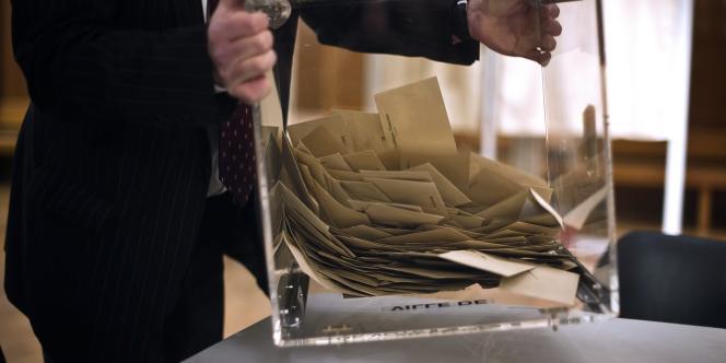 Un scrutateur vide l'urne contenant les bulletins de vote, le 20 mars 2011 dans un bureau de Dijon.