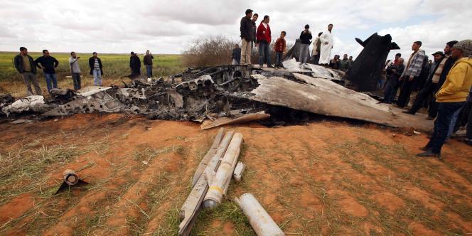 Des civils observent les restes du chasseur américain F-15 qui s'est craché dans la nuit de lundi à mardi.