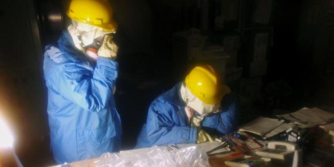 Sur cette photo diffusée par l'Agence japonaise de sûreté nucléaire, des techniciens récupèrent des données dans la salle de contrôle des unités 1 et 2.