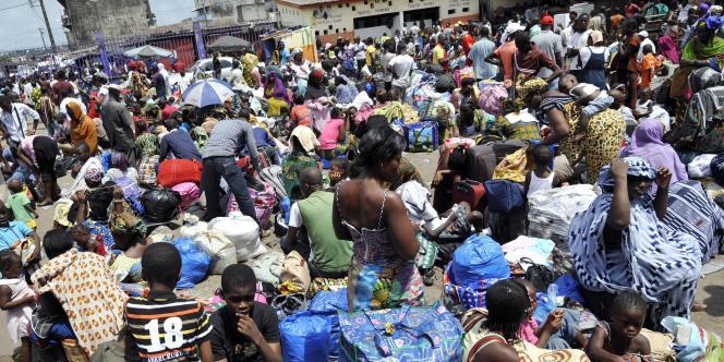Des habitants d'Abidjan attendent le bus pour fuir les violences.
