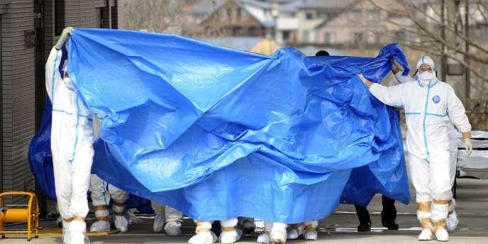 Des membres des forces d'autodéfense japonaises exposés aux radiations arrivent dans un hôpital de Fukushima pour subir une décontamination, le 25 mars 2011.