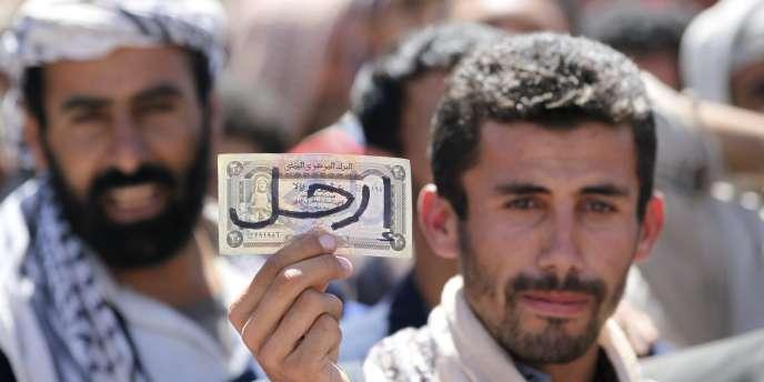 Un manifestant hostile au gouvernement brandit un billet de banque sur lequel est écrit