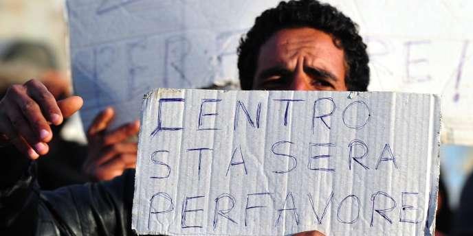 Un immigré tient une pancarte