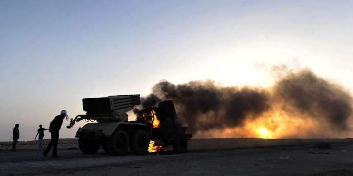 Des rebelles à proximité d'un lance-roquettes kadhafiste, à proximité de Ras Lanouf, le 27 mars 2011.