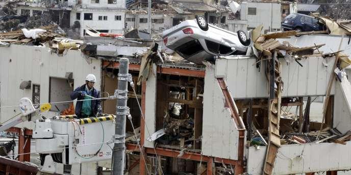 Des ouvriers tentent de réparer des lignes de courant dévastées par le séisme et le tsunami du 11 mars, à Onagawa, dans la préfecture de Miyagi.