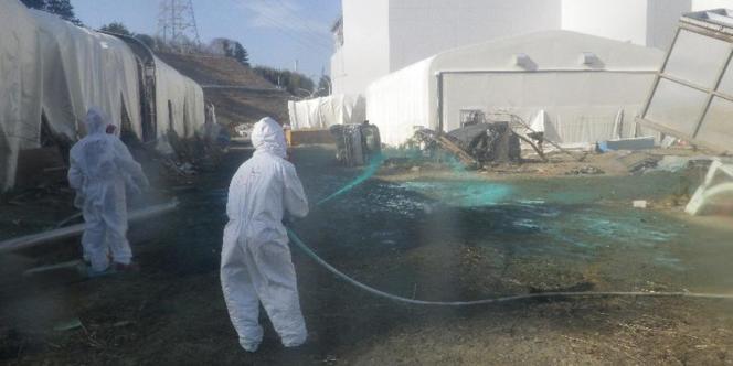 Les techniciens vaporisent, le 1er avril à Fukushima, une résine collante pour fixer au sol les poussières radioactives qui se sont éparpillées lors des explosions.