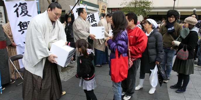 Le champion sumo Hakuo vient en aide aux victimes du tsunami à Tokyo le 24 mars.