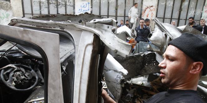 Des Palestiniens inspectent une voiture détruite par un tir israélien, le 9 avril 2011, à Gaza.