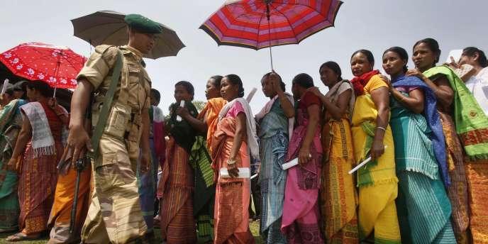 Un agent de sécurité patrouille devant des femmes de la tribu Bodo qui attendent de voter pour les élections législatives, près d'un bureau de vote dans le village de Jogeshpur, le long de la frontière entre l'Inde et le Boutan, à quelque 120 kilomètres à l'ouest de Gauhati.
