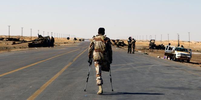 Un combattant insurgé amputé d'une jambe marche sur la route menant à Ajdabiya.