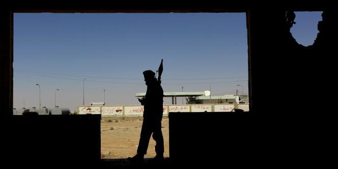 Un rebelle armé d'un lance-roquette dans les ruines d'un restaurant détruit des environs d'Ajdabiya, mardi.