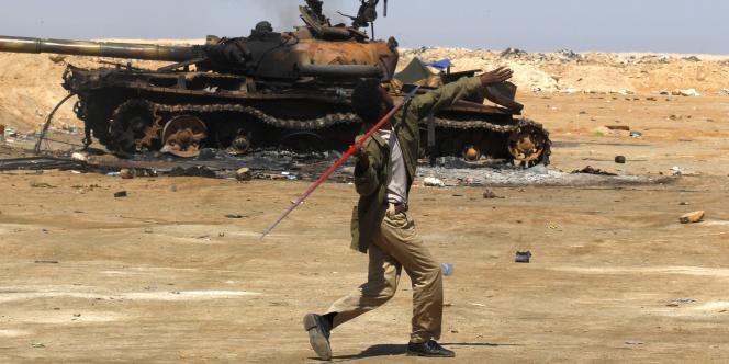 Un rebelle lance un javelot près d'un char détruit, mercredi.