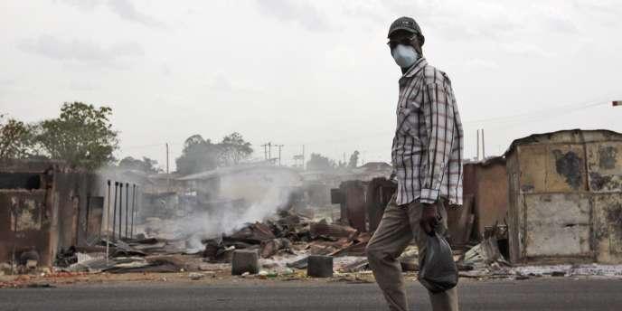 Un homme passe devant le marché incendié de Zonka, jeudi.
