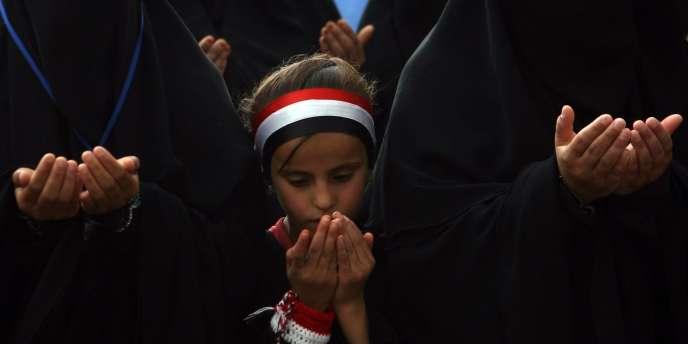 Une petite fille prie lors d'une manifestation anti-gouvernementale, dimanche à Sanaa.